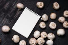 Cogumelos e nota frescos para o registro Foto de Stock Royalty Free