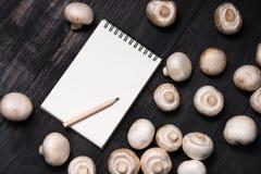 Cogumelos e nota frescos para o registro na tabela preta Fotografia de Stock Royalty Free