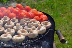 Cogumelos e tomates brancos do cogumelo na grade Foto de Stock