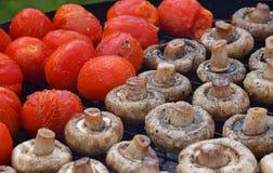 Cogumelos e tomates brancos do cogumelo na grade Imagem de Stock