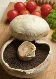 Cogumelos e tomates em uma placa de desbastamento. Fotografia de Stock