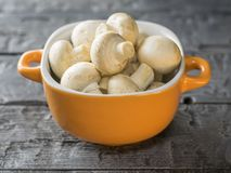 Cogumelos frescos em uma bacia amarela em uma tabela de madeira rústica O alimento do vegetariano está na tabela Fotos de Stock