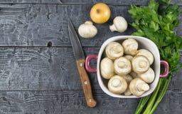 Cogumelos frescos em uma bacia e em uma faca roxas em uma tabela de madeira rústica O alimento do vegetariano está na tabela A vi Foto de Stock Royalty Free