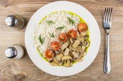 Cogumelos fritados com arroz e tomates na placa, sal, pimenta Fotografia de Stock