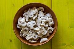 Cogumelos inteiros em uma bacia em placas de madeira Imagem de Stock