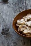 Cogumelos inteiros em uma bacia em placas de madeira Foto de Stock