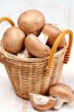 Cogumelos orgânicos em uma cesta no fundo de madeira branco Fotografia de Stock Royalty Free