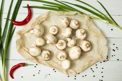 Cogumelos orgânicos frescos em um fundo de madeira branco, ao lado de uma pimenta de pimentão vermelho, de umas cebolas verdes e  foto de stock royalty free