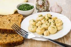 Cogumelos postos de conserva com aneto na placa, pão, verdes, condime Imagens de Stock