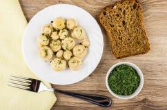 Cogumelos postos de conserva com aneto na placa, pão, verdes na bacia Imagens de Stock
