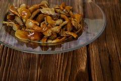 Cogumelos postos de conserva em uma placa transparente em uma tabela de madeira Fragmento do prato foto de stock royalty free
