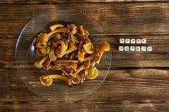 Cogumelos postos de conserva em uma placa transparente em uma tabela de madeira A inscrição com o nome do prato imagem de stock