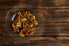 Cogumelos postos de conserva em uma placa transparente em uma tabela de madeira Vista de acima imagens de stock royalty free