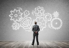 Cogwheel engine drawn on concrete wall as symbol for teamwork and cooperation. Back view of businessman looking at wall with drawn gear mechanism Royalty Free Stock Photo