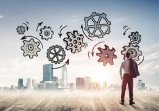 Cogwheel engine drawn on screen as symbol for teamwork and coope. Back view of businessman looking at modern city and drawn gear mechanism Stock Image