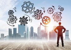 Cogwheel engine drawn on screen as symbol for teamwork and cooperation. Back view of businessman looking at modern city and drawn gear mechanism Stock Photo