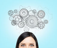 Cogwheel mechanism. A young woman thinking about a watch mechanism, a picture of cogwheels over her head. Front view, only eyes seen. Blue background. Concept of stock photography