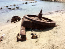 Cogwheel of old ship stranded on beach with plastic bottle garbage Royalty Free Stock Photos