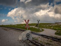 Cogwheel railway crossing with Saint Andrew`s Cross near Hochschneeberg with cloudy sky in the scenic sunset royalty free stock photography