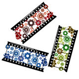 Cogwheels on a filmstrip. Gears on filmstrips in red, green and blue over white background Royalty Free Stock Images