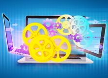 Cogwheels, gear flying in front of laptop and a Royalty Free Stock Image