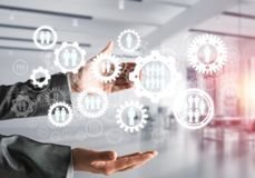 Cogwheels and gears mechanism as social communication concept. Business woman in black suit keeping white social gear icons in hands with office view and Stock Photography