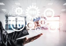 Cogwheels and gears mechanism as social communication concept. Business woman in black suit keeping white social gear icons in hands with office view and Stock Photos