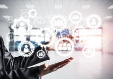 Cogwheels and gears mechanism as social communication concept. Business woman in black suit keeping white social gear icons in hands with office view and Stock Images