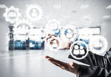 Cogwheels and gears mechanism as social communication concept. Business woman in black suit keeping white social gear icons in hands with office view on Stock Image