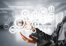 Cogwheels and gears mechanism as social communication concept. Business woman in black suit keeping white social gear icons in hands with office view on Stock Photography