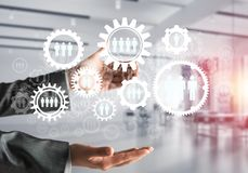 Cogwheels and gears mechanism as social communication concept. Business woman in black suit keeping white social gear icons in hands with office view and Royalty Free Stock Photos