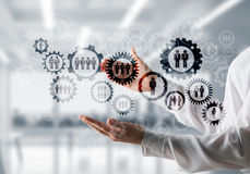 Cogwheels and gears mechanism as social communication concept. Business woman in white shirt keeping black social gear icons in hands with office view on Stock Photo