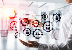 Cogwheels and gears mechanism as social communication concept. Business woman in white shirt keeping black social gear icons in hands with office view and Royalty Free Stock Photo