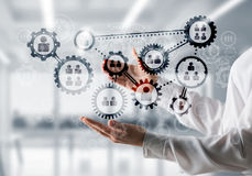 Cogwheels and gears mechanism as social communication concept. Business woman in white shirt keeping black social gear icons in hands with office view on Stock Photography