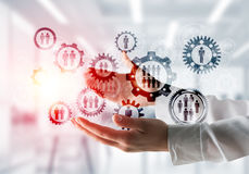 Cogwheels and gears mechanism as social communication concept. Business woman in white shirt keeping black social gear icons in hands with office view and Royalty Free Stock Images