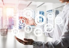 Cogwheels and gears mechanism as social communication concept. Business woman in white shirt keeping white social gear icons in hands with sunlight and office Stock Photography