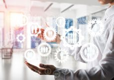 Cogwheels and gears mechanism as social communication concept. Business woman in white shirt keeping white social gear icons in hands with sunlight and office Royalty Free Stock Photo
