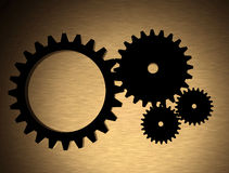 Cogwheels over a gold metal texture Stock Images