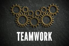 Cogwheels symbolizing teamwork as a connected network of people. On slate background royalty free stock photos