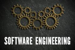 Cogwheels and the words `software engineering` symbolizing a complex system working together. Cogwheels and the words `software engineering` on slate background royalty free stock images