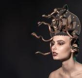 Coiffe de méduse de fille de couleur d'or sur un fond noir Photo stock