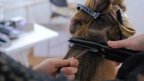 Coiffeur à l'aide du redresseur sur de longs cheveux de client dans le salon de coiffure clips vidéos
