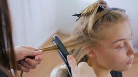Coiffeur à l'aide du redresseur sur de longs cheveux de client dans le salon de coiffure banque de vidéos