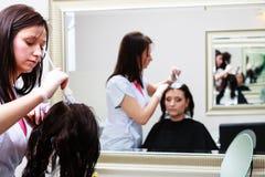 Coiffeur appliquant le client féminin de couleur au salon, faisant la teinture capillaire photo stock
