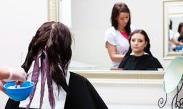 Coiffeur appliquant le client féminin de couleur au salon, faisant la teinture capillaire images stock