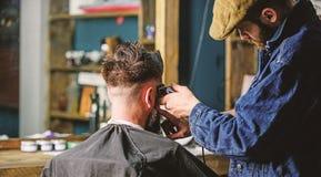 Coiffeur avec des cheveux de r?glage de tondeuse de client, vue arri?re Concept de processus fonctionnant Le coiffeur avec la ton images stock