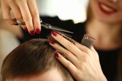 Coiffeur avec des ciseaux coupant les cheveux masculins de Brown photos libres de droits