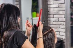 Coiffeur avec les mains tatouées coupant et modelant les cheveux bruns images stock