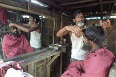 Coiffeur bangladais au travail dans le raseur-coiffeur dans Dhaka Image libre de droits
