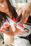 Coiffeur coupant les cheveux foncés utilisant des ciseaux professionnels Photographie stock